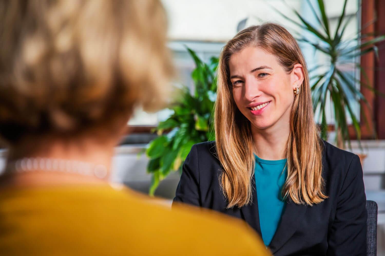 Das Bild zeigt den lächelnden Coach Katrin Bergmann und die Kundin während einer Coaching Session mit dem Thema Konfliktlösung.