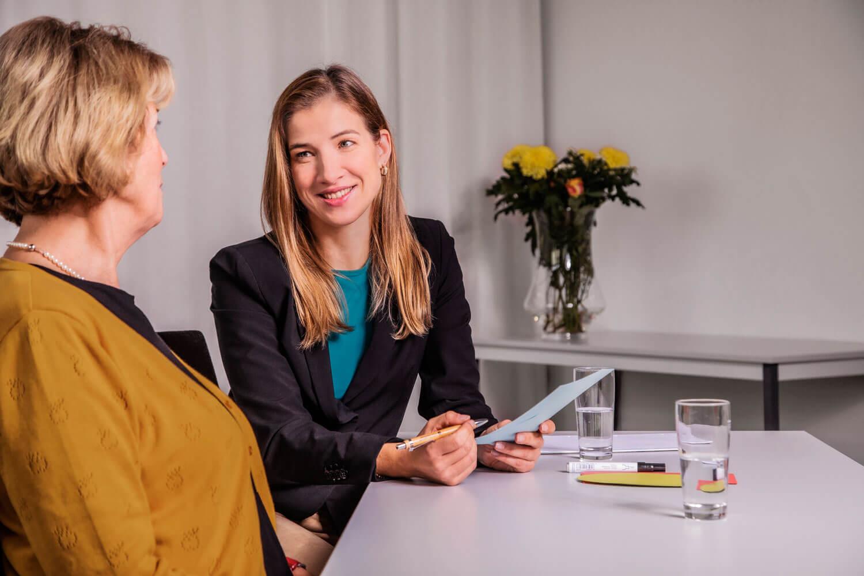 Das Bild zeigt einen hellen Raum, in dem der Coach Katrin Bergmann und die Kundin lösungsorientiert am Ziel der Stressreduktion arbeiten.