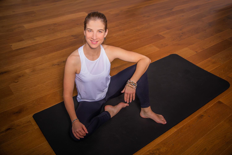Das Bild zeigt die lächelnde Coyoflow Gründerin Katrin Bergmann in entspannter Sitzhaltung auf der Yogamatte im Yoga und Coaching Raum.