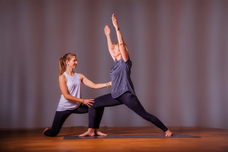 Das Bild zeigt die individuelle Yogapraxis während die Yoga Personal Trainerin Katrin Bergmann die Heldenstellung bei der Yoga Teilnehmerin korrigiert.