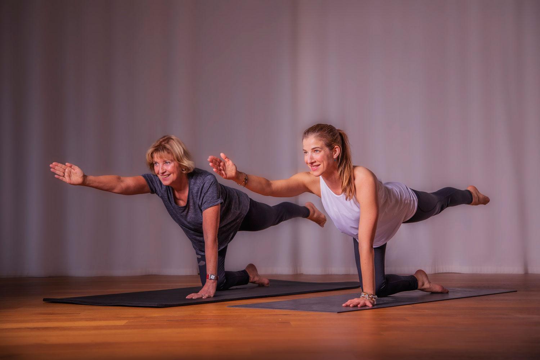 Das Bild zeigt die Yoga Personal Trainerin Katrin Bergmann und Yoga Teilnehmerin bei einer Achtsamkeitsübung in einer Vierfüßlerstand Variation beim Yoga Personal Training.