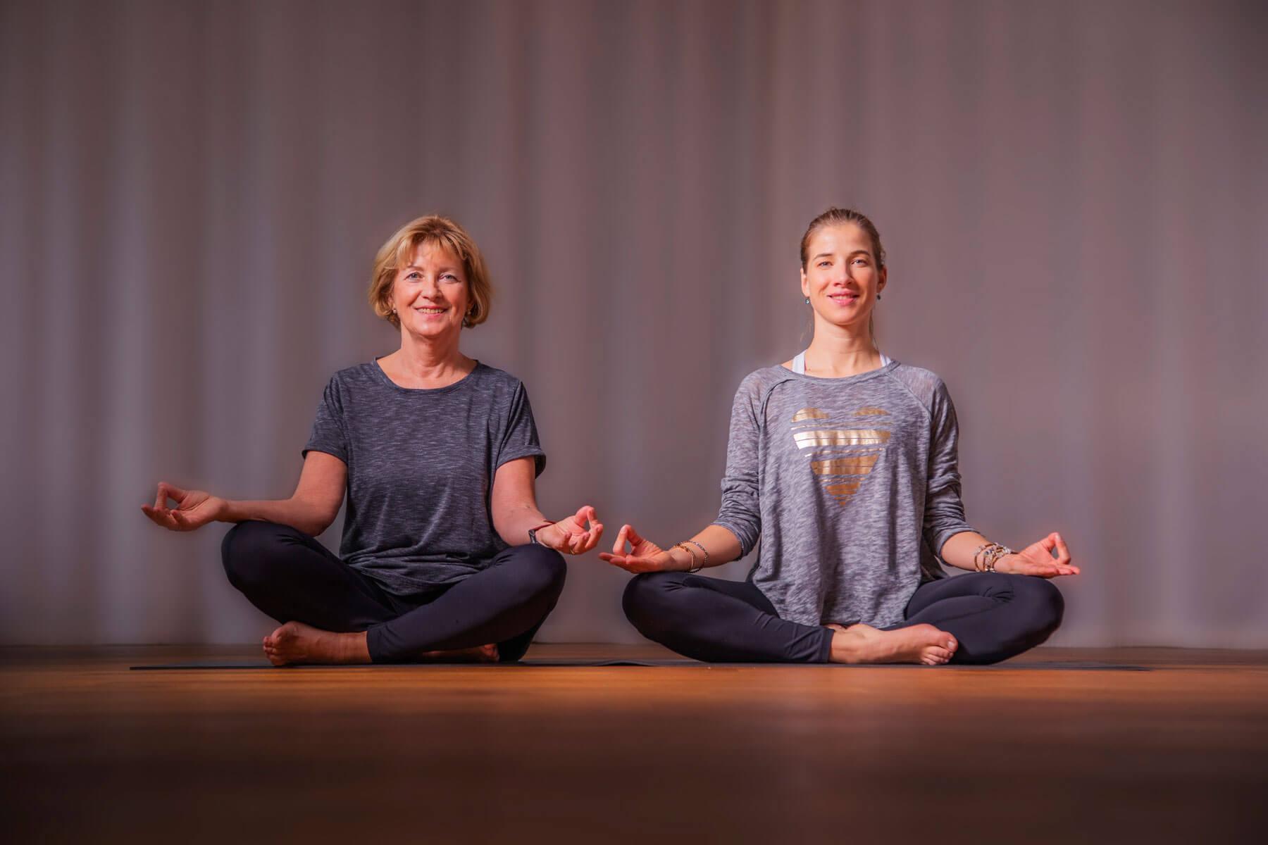 Das Bild zeigt die Yoga Personal Trainerin Katrin Bergmann und die entspannt lächelnde Kundin im Yoga Meditationssitz.